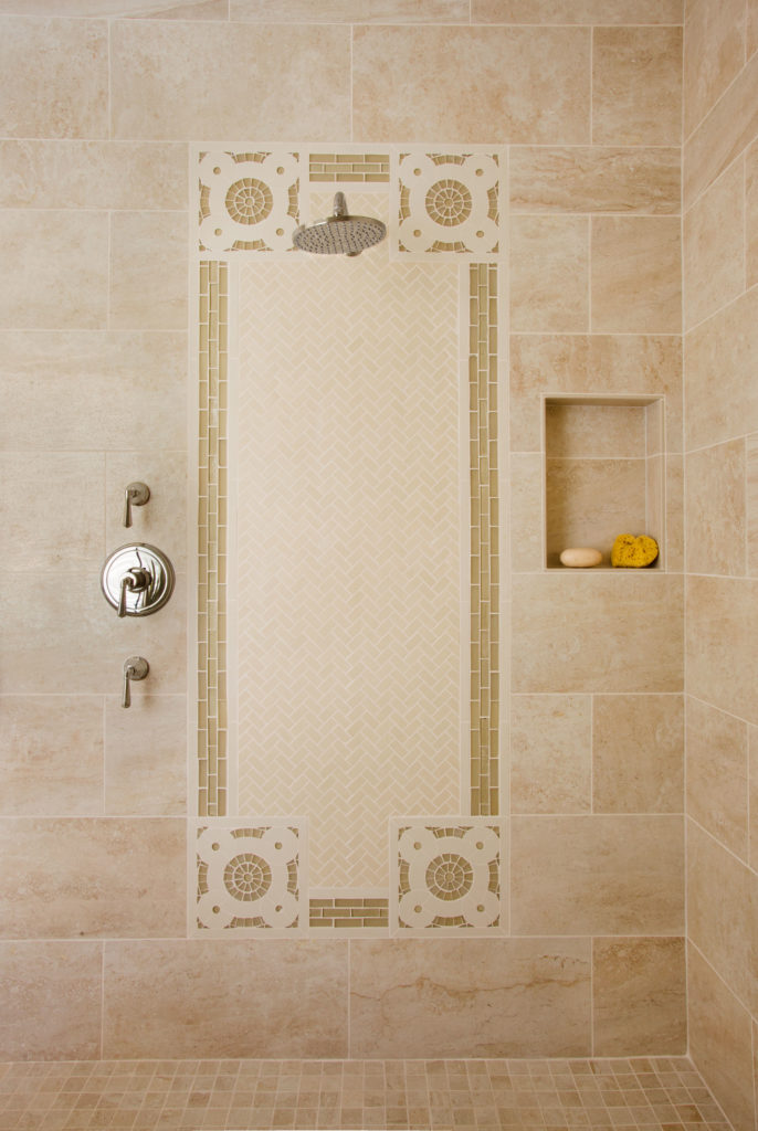 A view of the shower, which features the same tile pattern as the floor of the bathroom.