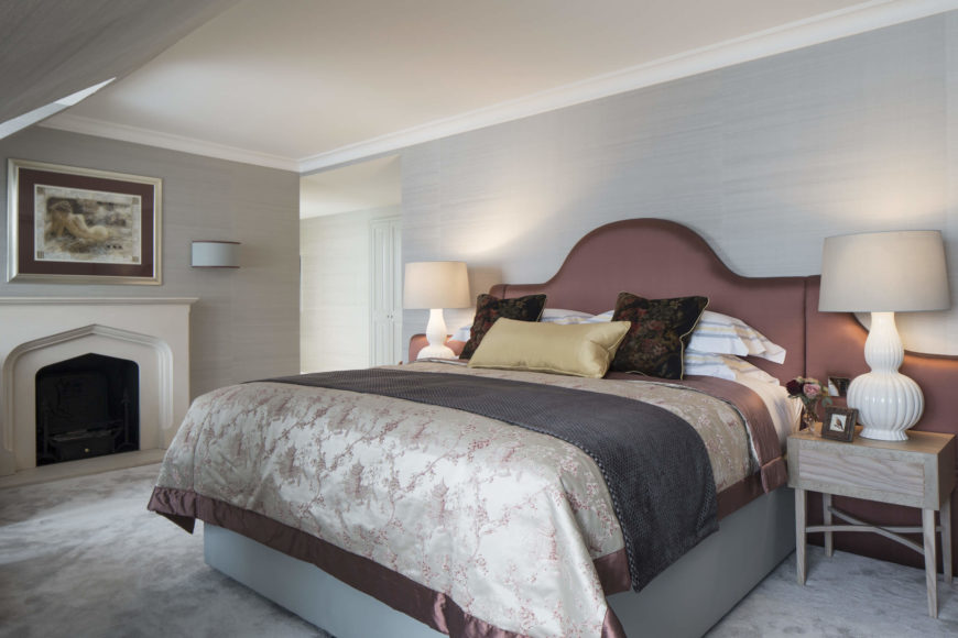 Master bedroom holds a grandly appointed bed with dark salmon headboard between a pair of natural wood bedside tables, as well as a full fireplace at left.