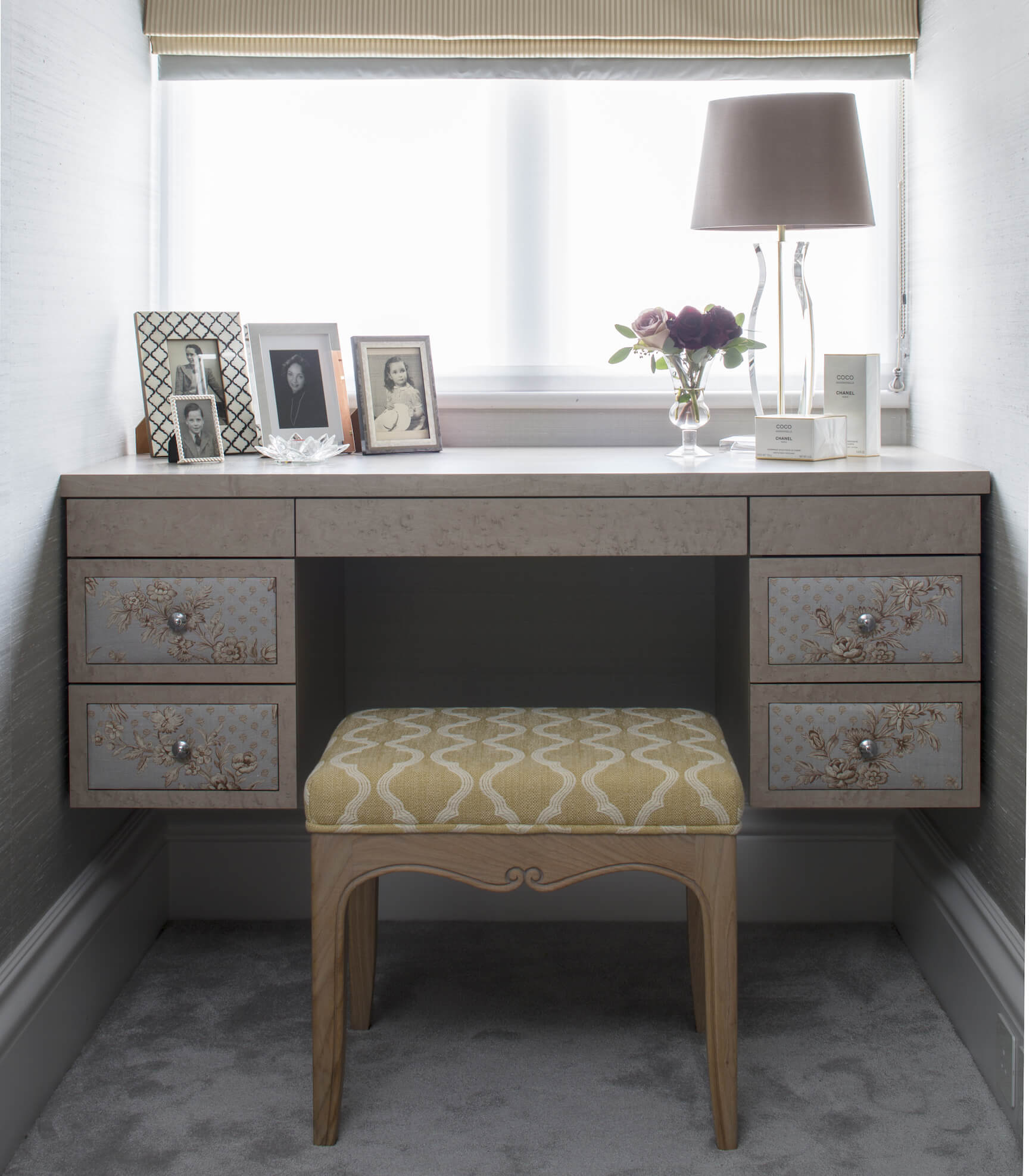 Bedroom features this cozy floating powder room desk, with floral patterned drawers, below a window. Natural wood frame bench chair with gold patterned seating stands below.