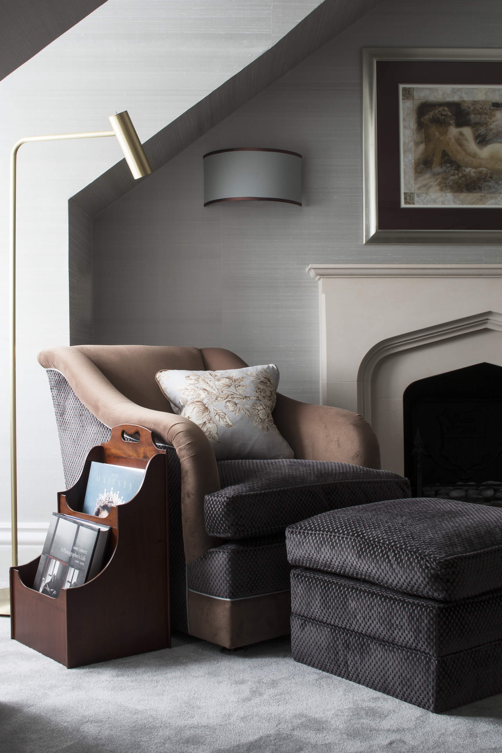 Beside the master bedroom fireplace, we find this rich multi-textured club chair with matching ottoman, below a gold hued floor lamp and half-cylinder sconce.
