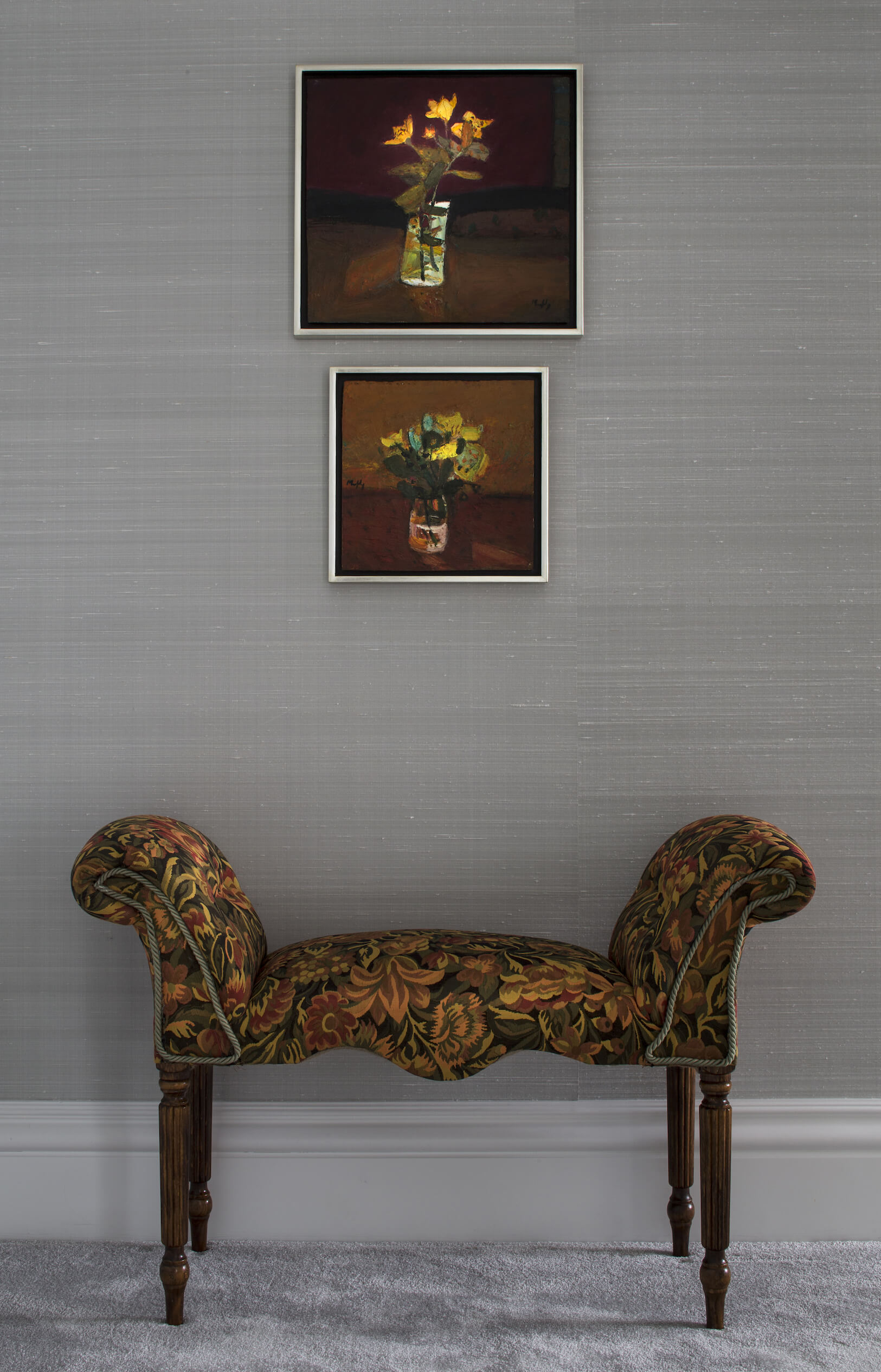 Another example of the interplay of rich detail and soft neutral tones is this backless armchair with floral upholstery and carved wood arrow feet, standing below a pair of paintings in matching tones.
