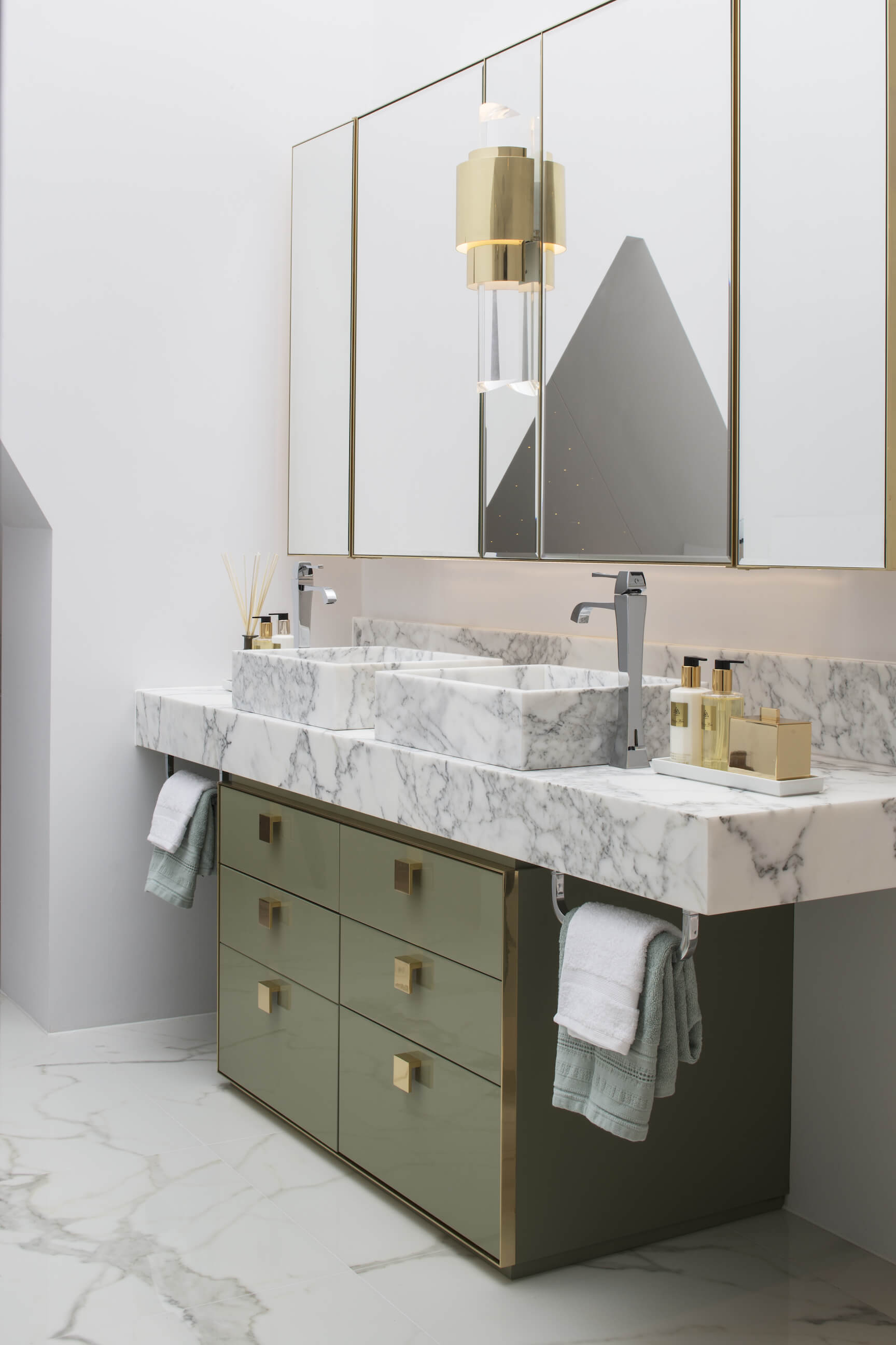 The lavish vanity with marble countertop and pair of vessel sinks stands over rich green cabinetry with gold hardware.