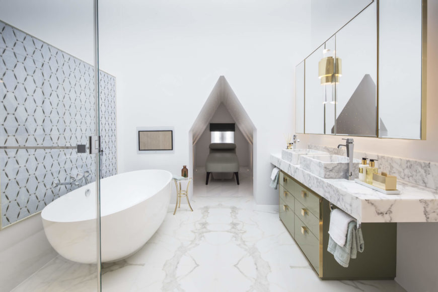 The master bathroom features a sumptuous mixture of marble and gold detail, within a stark white space. Rounded pedestal tub at left stands across from a dual vanity over green cabinetry, with gold hardware throughout. At center is a small relaxation cubby space.