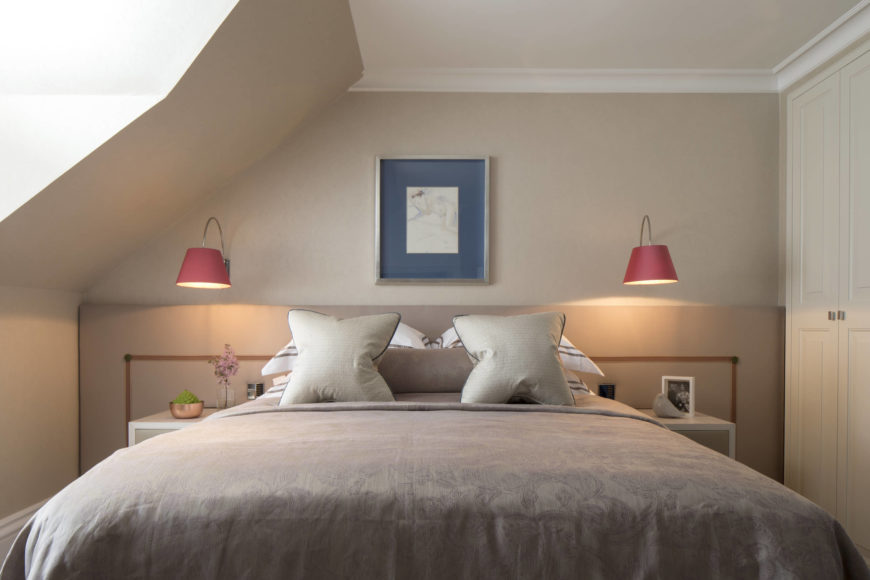 Secondary bedroom features warmer appointments, with a neutral toned bed and walls, framed by a pair of white structure bedside dressers and light salmon hued sconces.