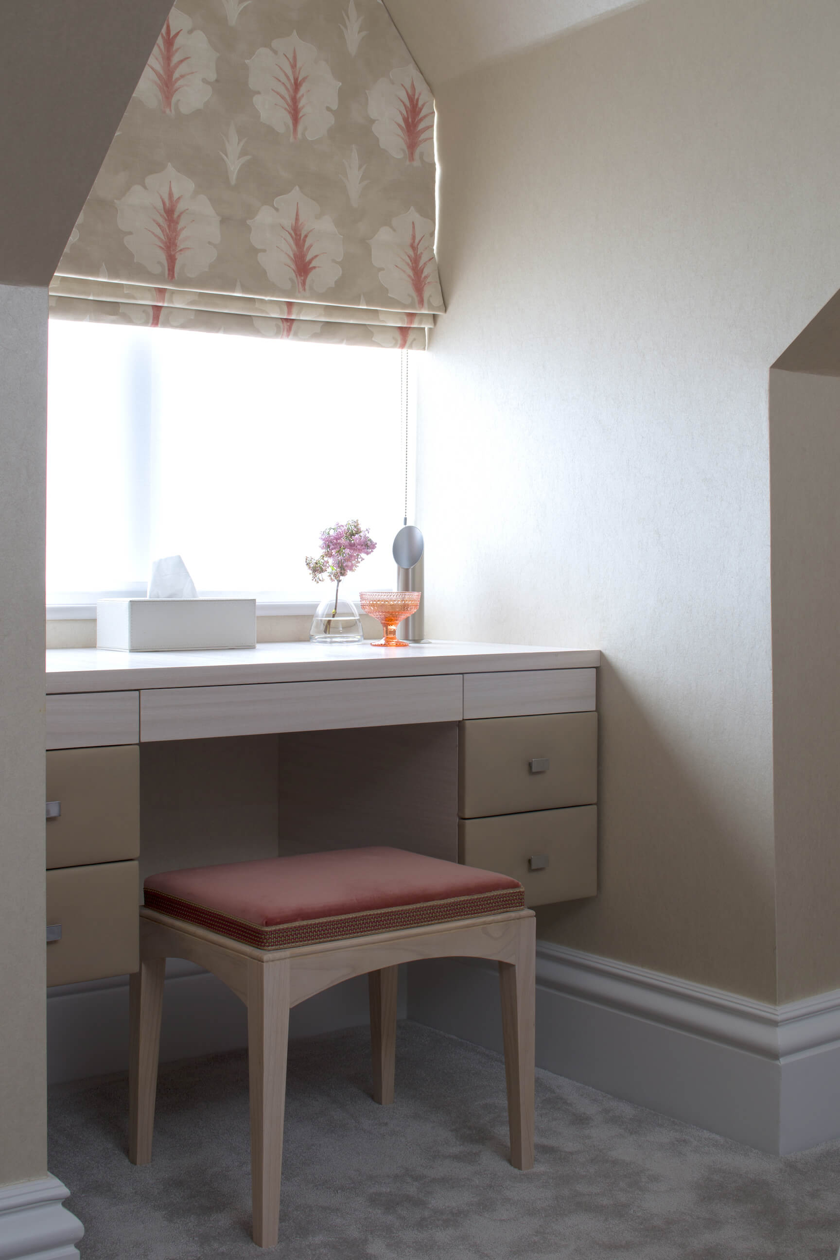 Continuing with the mixture of light salmon tone and white with beige walls, the powder room space here features another floating desk below a small private window.