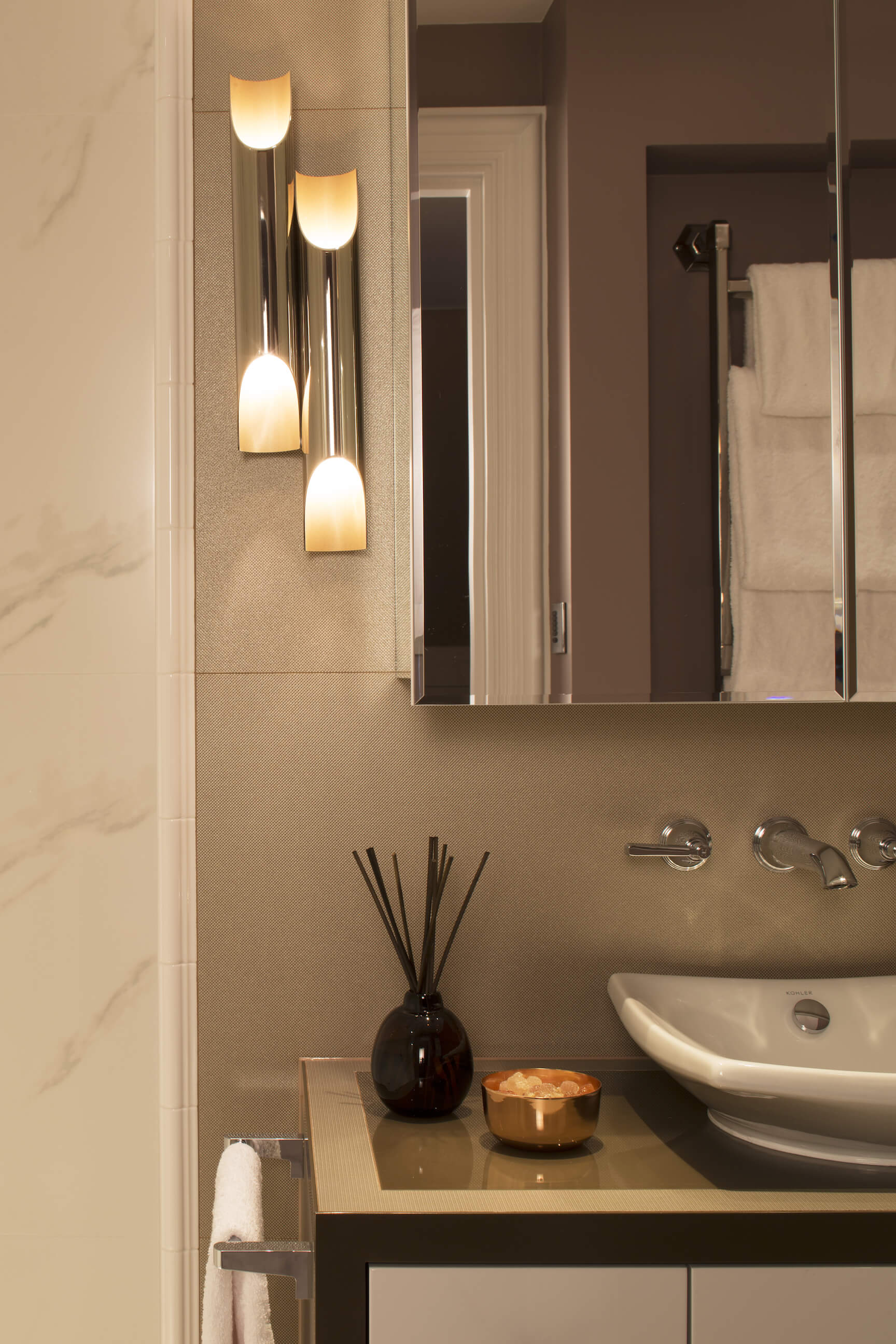 Chromed cylinder sconces flank the mirror in this bathroom, while wall-mounted plumbing floats above the vessel sink.