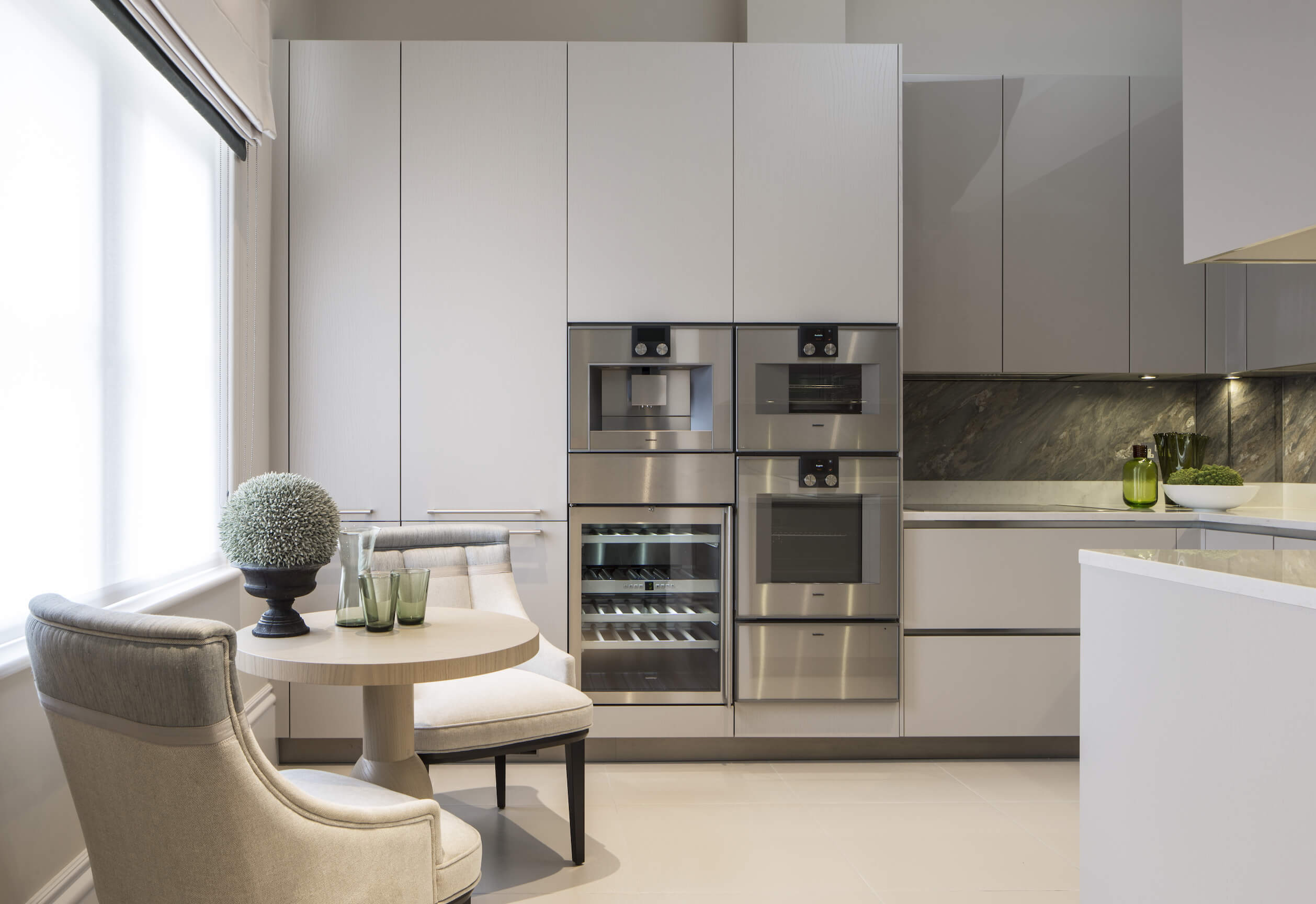 The sleek, minimalist kitchen contains tall off-white cabinetry and stainless steel appliances, contrasting with dark marble backsplash. A pair of chairs matching the dining set wrapps a small circular wood table at left.