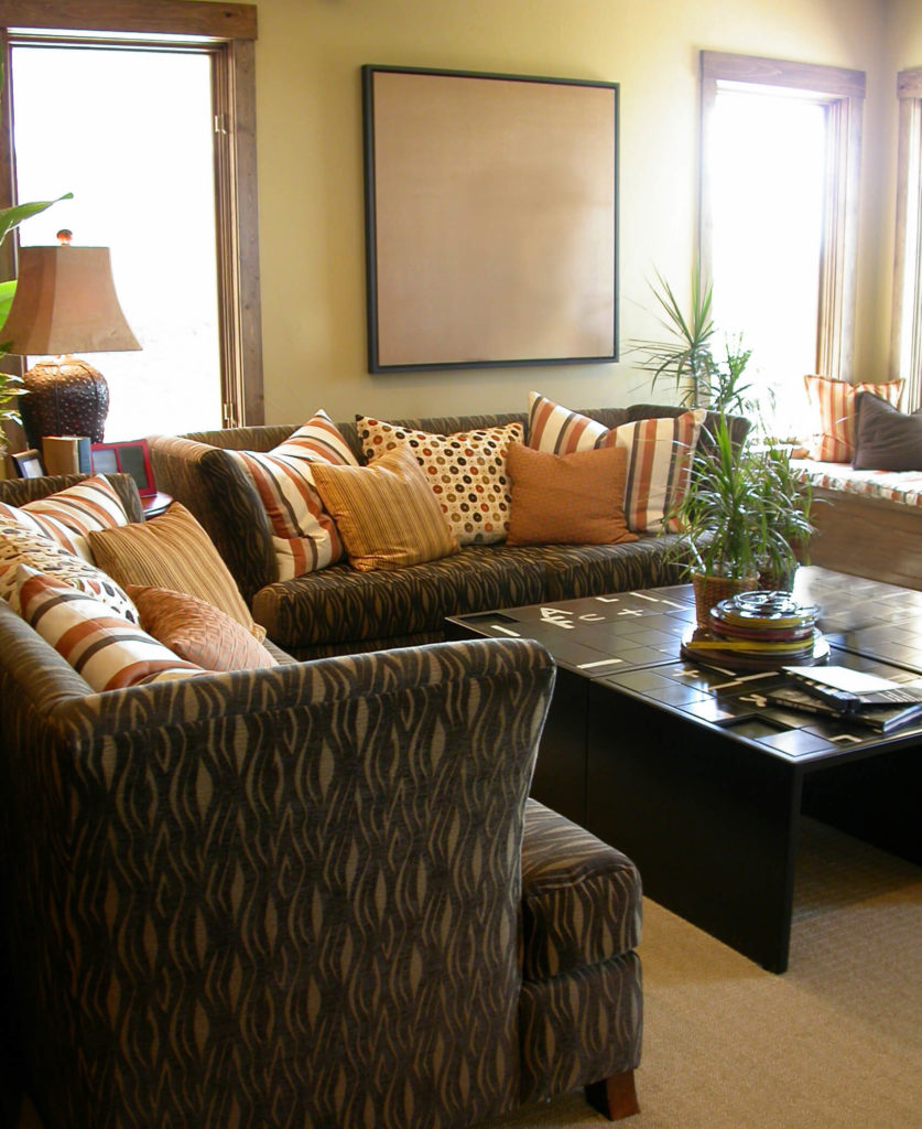 A Living Room With A Unique Puzzle Coffee Table And Dark Upholstered  Furniture That Contrasts With