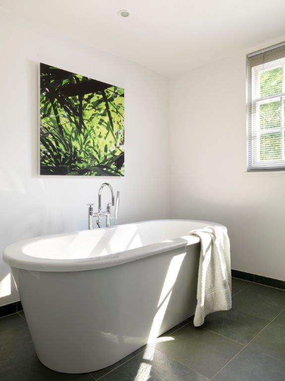 The large, deep, luxurious soaking tub in the master bathroom, freestanding on dark charcoal tiles. A single painting of lush foliage is on the wall behind the tub.