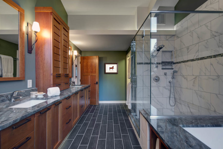 The spacious master bathroom has gray granite countertops and an enclosed soaking tub. The sinks are separated by custom hardwood cabinetry, with a towel cabinet in between.