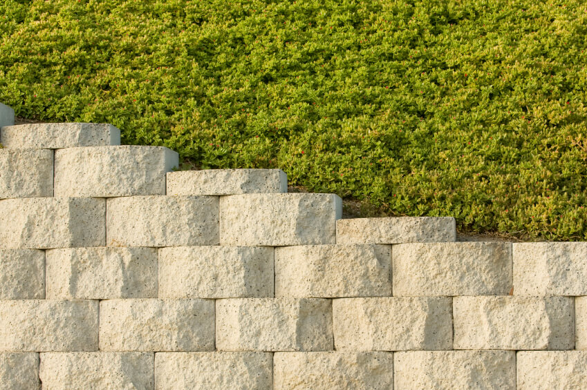 A retaining wall of light stacked stone that is uniform in color and size. The ground above the stones is covered in a thick groundcover.