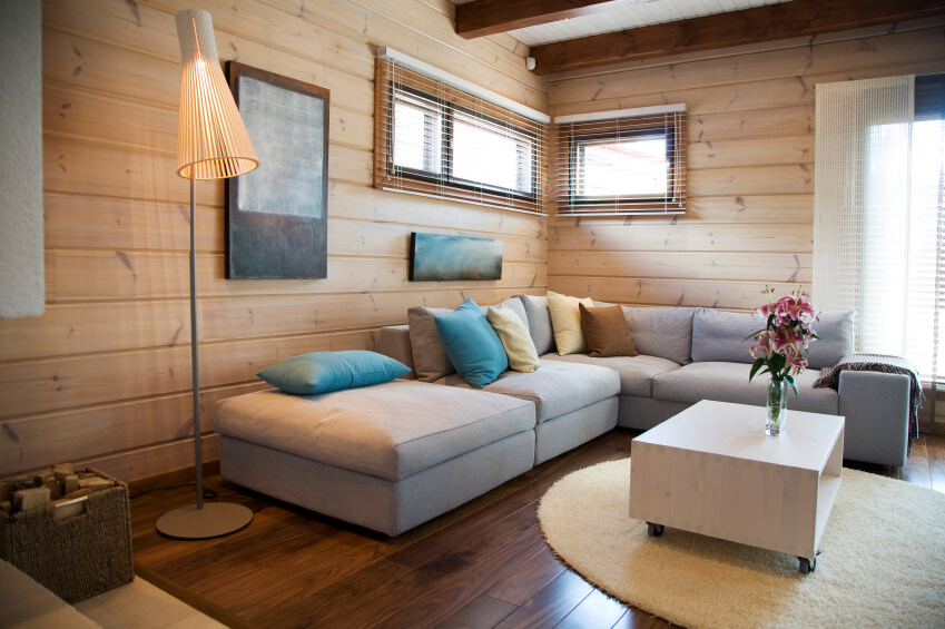 "A chic and minimalist living room with light wood paneling and a wheeled coffee table with a single glass vase. The light gray couch has turquoise, pale yellow, and brown throw pillows. The mixture of the wood panelling and the minimalist makes this space a ""modern contemporary cabin."""