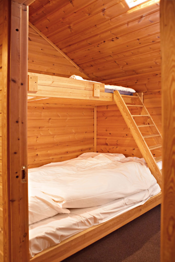 A bedroom constructed of knotty pine creates a rustic backdrop for a bunk bed and simple white bedding to put guests up for a night.