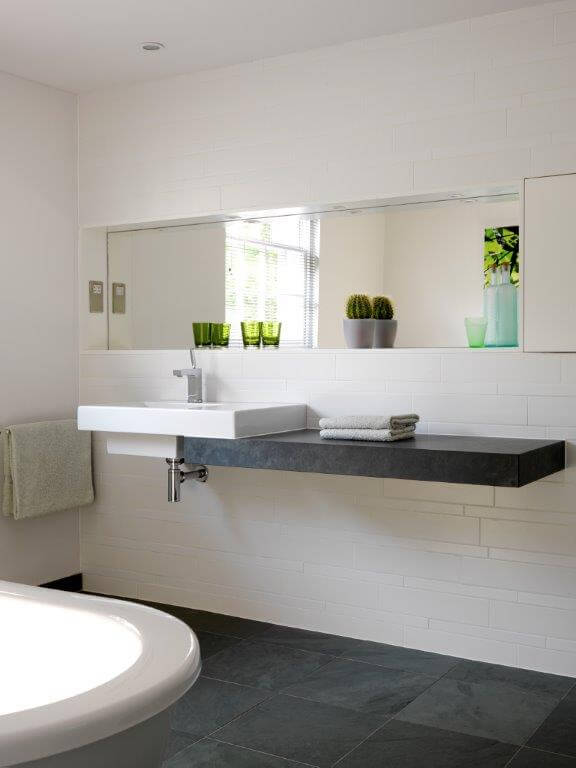 A view from the bathtub to the floating single vanity on the opposite side of the room, which runs under half of the wall-mounted sink. A shelf above the sink with an inset mirror is built into the wall and acts as additional storage.
