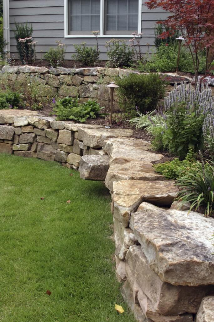 a hand laid retaining wall made out of natural stone two terraces are filled - Landscape Design Retaining Wall Ideas