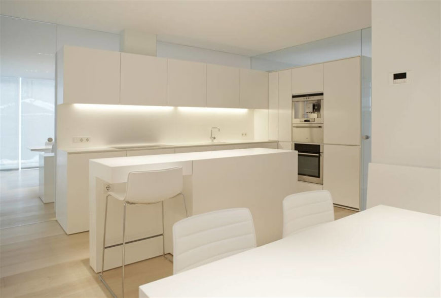 An Entire Kitchen And Dining Room In Pristine White. The Kitchen Is Divided  Into Two