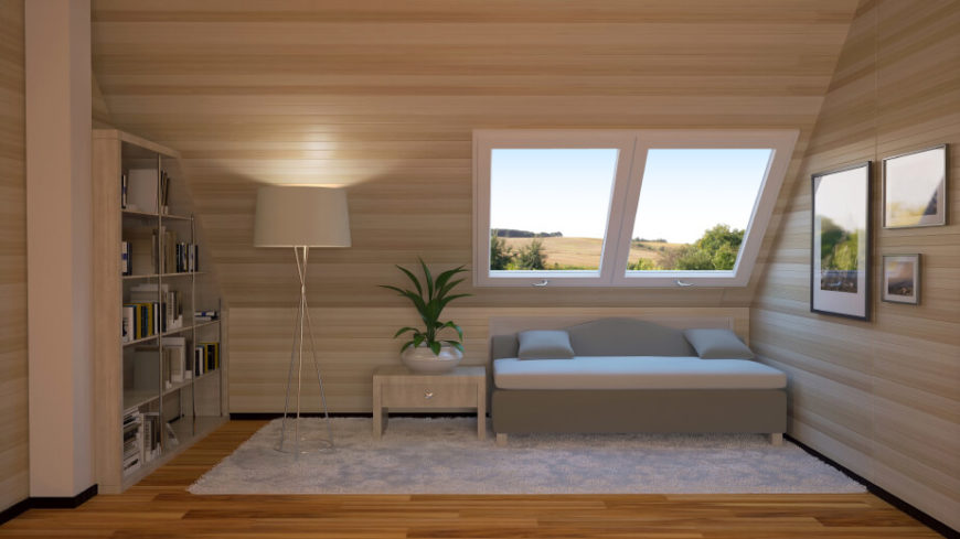 A smaller attic space with skylights above the futon. Light wood on the walls and ceiling is contrasted by the warmer toned wood flooring.