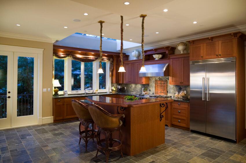 Lengthy pendant lights hang in a trio above the curved, polished wooden island with black iron accents. A gorgeous skylight above the sink area lets in natural light to brighten the small kitchen.