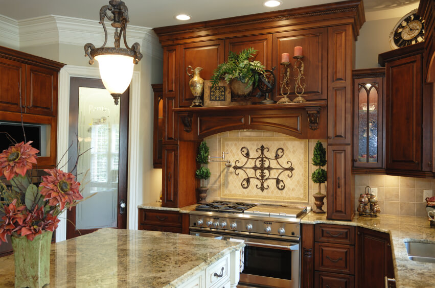 An Old World Style Dark Wood Kitchen With Light Marble Countertops And A  Beige Stone