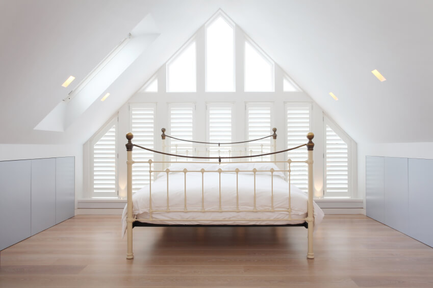 A Bedroom Offers A Simple Cream Iron Bed Frame And A Wall Of Shuttered  Windows.