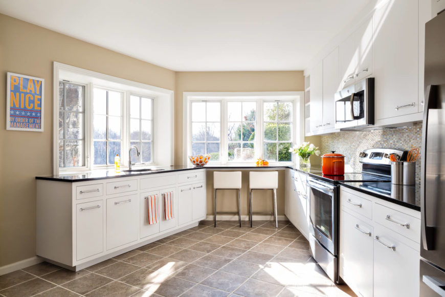 """The airy kitchen is situated in an interesting section of the home that narrows towards the eat-in bar, taking the """"kitchen triangle"""" to a whole new level. The high end appliances and white cabinets give this kitchen a bright, shiny, feeling of perfection."""
