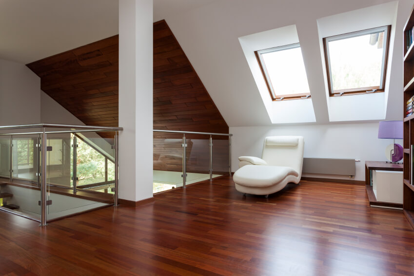 The rich hardwood floors of this attic match the panelling on part of the ceiling. A glass railing blocks off the loft from the staircase and the space below.