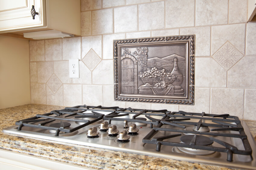 a ceramic tile backsplash with a metal medallion above the range in a pastoral scene - Ceramic Tile Kitchen Backsplash