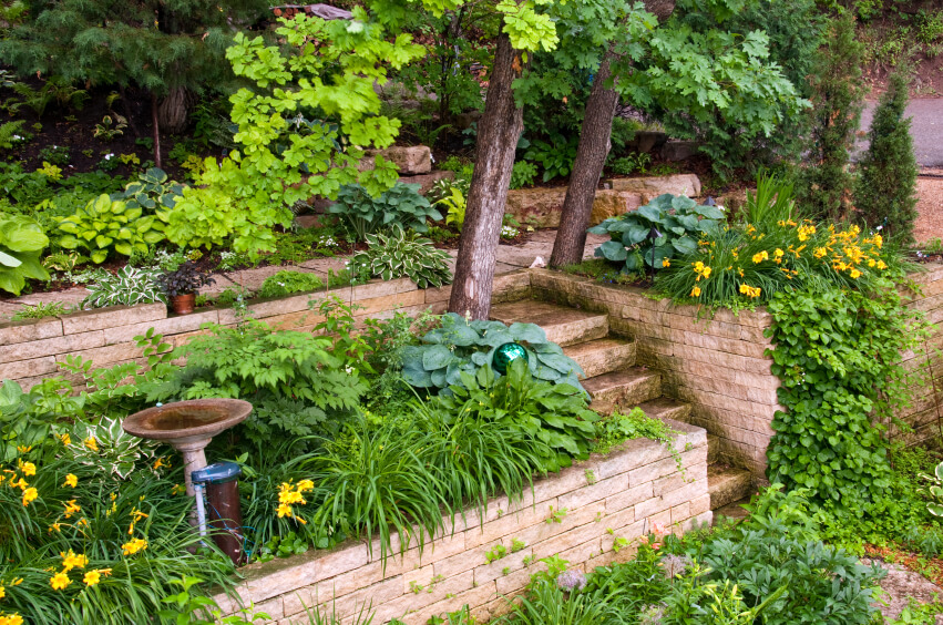 Lush landscaping with a small birdbath, looking glass, and uniformly stacked stones. A small set of stairs leads up to a pathway on the top terrace.