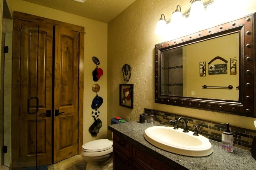The adjoining boy's bathroom has a bronzed mirror above the sink with circular accents. Accents in this room include a sports-themed wall hanging set and other sports-themed wall decorations.
