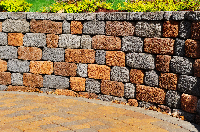 A retaining wall next to a stone courtyard in alternating red and gray stone.