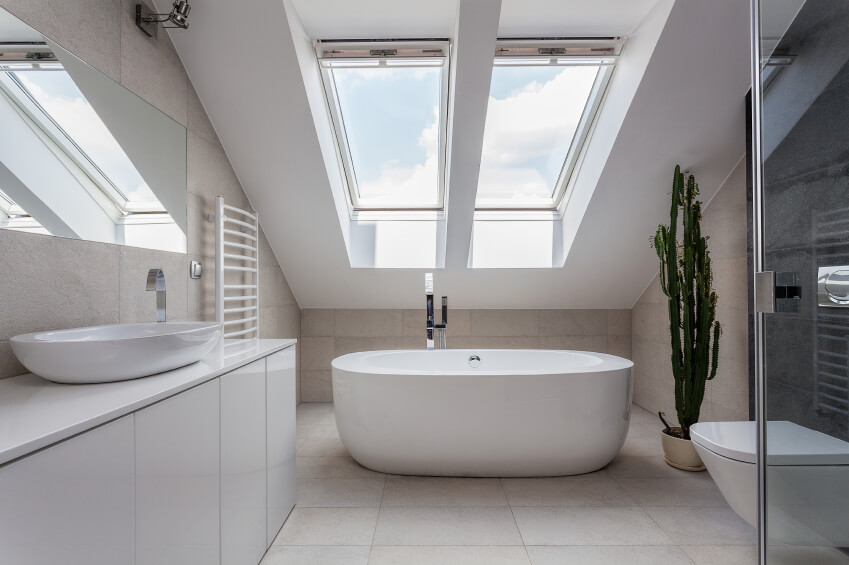 A white bathroom with sleek modern fixtures and two skylights above the deep soaking tub. A large cactus adds a bit of color to the neutral room.
