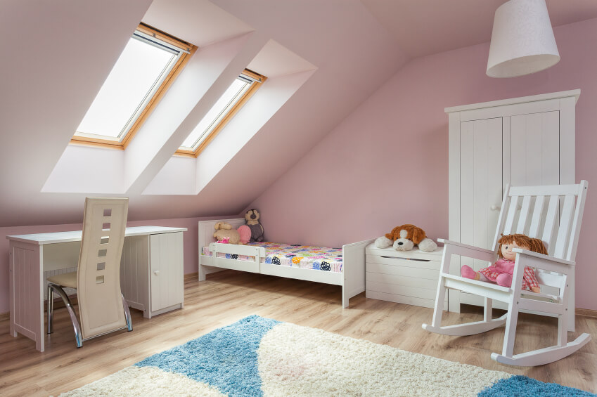A sweet child's room in pale pink and white. The rocking chair appears to be oversized in comparison with the miniature bed tucked into the corner.