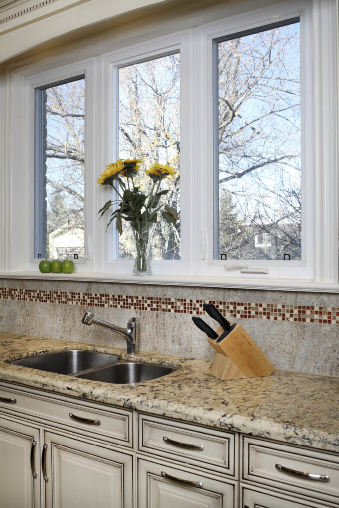 A Solid, Seamless Stone Backsplash With A Strip Of Cream, Gray, And Red