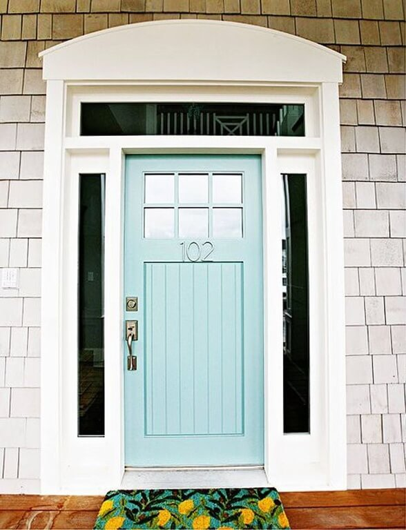 A wooden powder blue front door with glass panels on either side. The door has a brass lock and handle. It also has a door number in the center in a matching shade of blue. It also features a glass transom window right above the door and a pair of sidelight windows. In front of the door there is wood flooring and a doormat with floral designs.