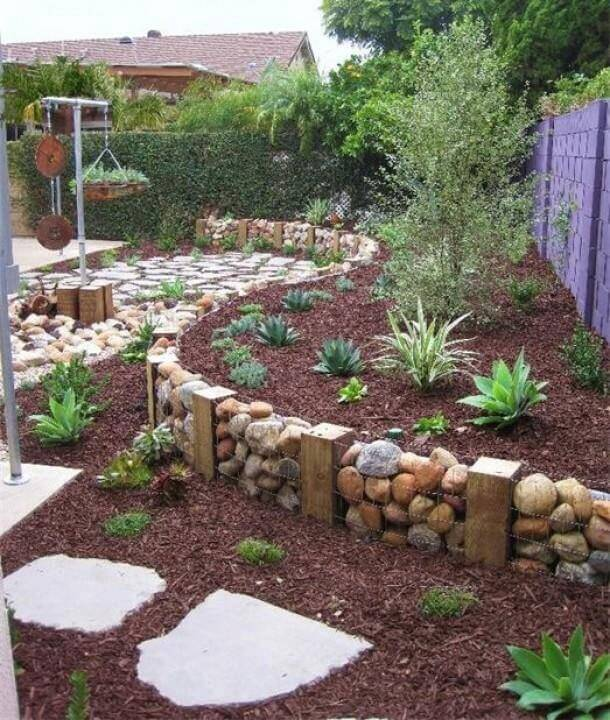 a simple terrace created with wooden blocks chicken wire and large stones for a