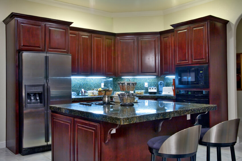 A small eat-in kitchen with rich cherry wood cabinets and stainless steel appliances. The green-gray granite countertops almost glow when lit up by the under-cabinet lighting. The small kitchen island plays host to two modern-style barstools with metallic backs.