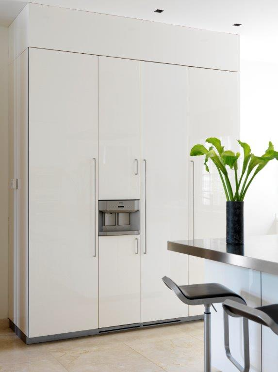 A close up on the refrigerator that has been cleverly merged with the cabinetry for a truly seamless appearance.