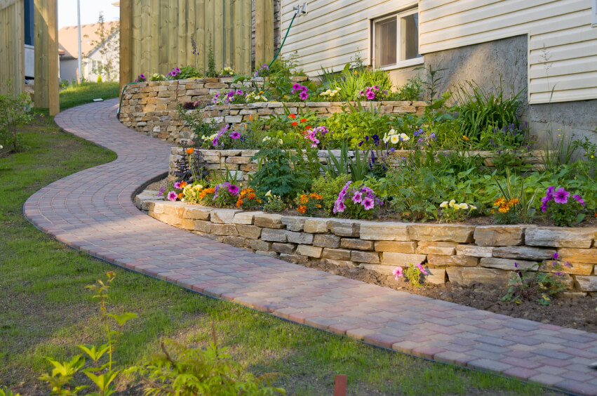 a residential terrace garden along a winding stone path along the side of the home