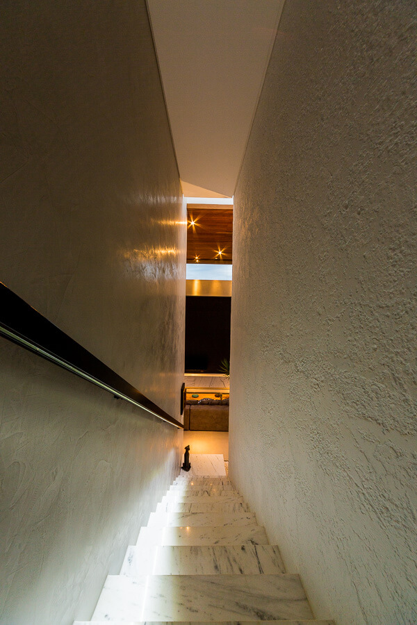 This lengthy marble staircase leads up and away from the grand living room.