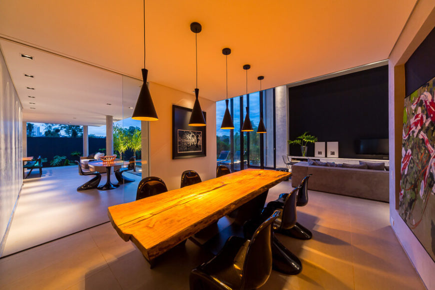 The dining room, connected to the main living room, holds a large single-piece wood dining table surrounding by black modernist chairs. The room is lit via series of conical pendant lights in black.