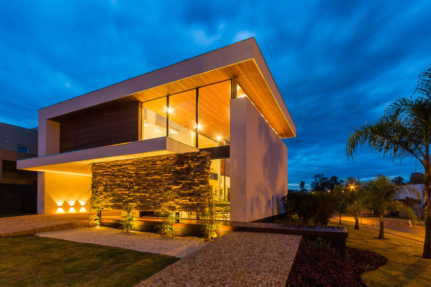 The singular stone brick wall floating in front of the glass wrapped home adds a layer of textural interest, contrasting with the sleek shape of the building.