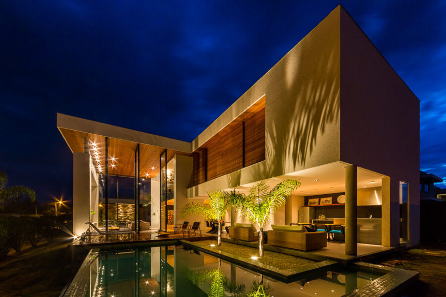 The L-shape of the home wraps this luxurious pool area and extensive patio. We see the kitchen and relaxing indoor space at right, fully open to the outdoors.