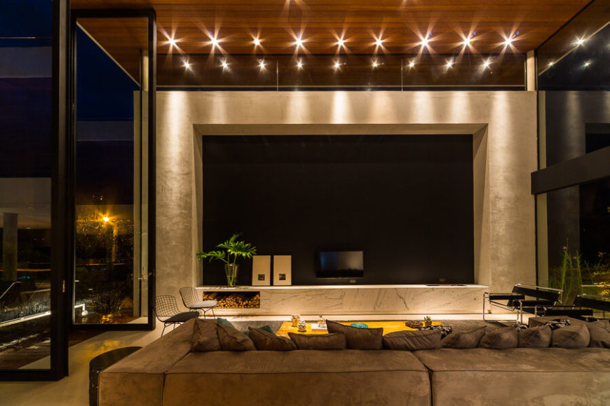 """The full height glass and elevated, """"floating"""" ceiling in the grand room create a sense of outdoors comfort, and add a striking look to the home."""