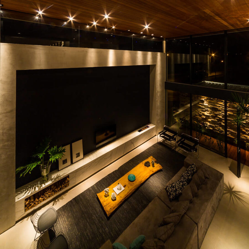Seen from above, the sprawling living room glows with expanses of concrete, marble, and grey fabrics beneath the constellation of recessed lighting.