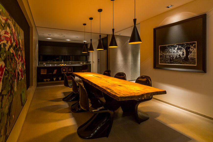 The dining room is defined by large wall mounted art pieces and the lengthy natural wood table, a theme seen already in the living room.