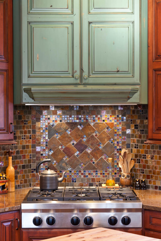 A glass tile backsplash with multiple colored tiles