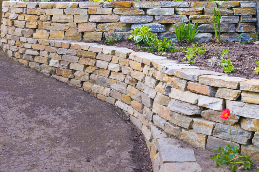 stone retaining walls running beside a packed dirt road - Retaining Walls Designs