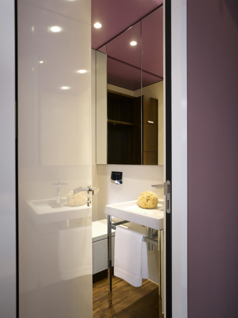 The small attached bathroom houses a metal frame vanity and large frameless mirrors.