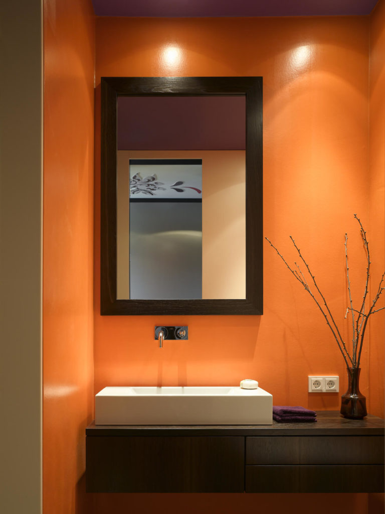 Master bath pops in bright orange and purple tones. Here is the floating dark wood vanity holding a large rectangular vessel sink.