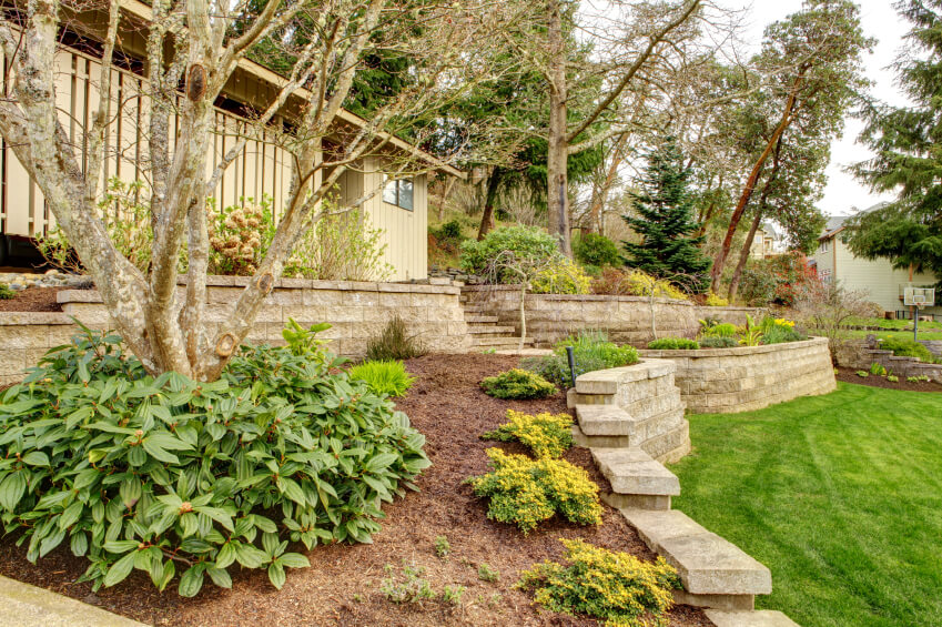 a contemporary home with terraced landscaping on either side of the stone stairs that lead up - Landscape Design Retaining Wall Ideas